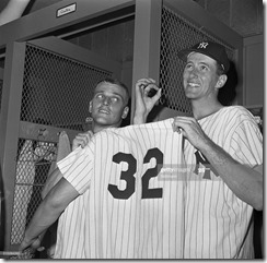 (Original Caption) N.Y. Yankee slugger Roger Maris (left), ably assisted by teammate pitcher Roland Sheldon, holds up shirt with number 32 on its back, indicative of the number of home runs Maris has hit thus far this season. The reason for Sheldon's zeroed fingers and far-off look is because he got his first major league shutout July 5th, by pitching the Yankees to a four-hit 6-0 victory over the Cleveland Indians at Yankee Stadium here.